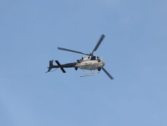 A police helicopter assists in the search for a suspect