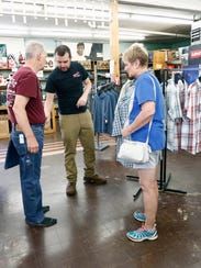 Store manager Tom Herbst helps a customer make a selection