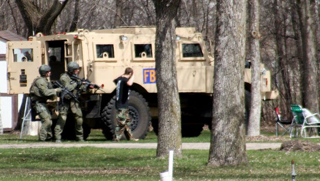 "This May 3, 2013, photo provided by Jeremy Jones shows authorities with Buford Rogers, right, who belongs to a tiny local militia, during a raid on a mobile home in Montevideo, Minn. Rogers, 25, is scheduled to be sentenced Monday, April 28, 2011 after pleading guilty to one count of possessing a firearm illegally and one count of possessing an unregistered destructive device, namely ""two black powder and nail devices,"" which he admitted he made himself. Prosecutors are seeking more than five years in prison, arguing that Rogers poses a threat to public safety, noting the items were designed solely to injure people. (AP Photo/Montevideo American-News, Jeremy Jones, File)"