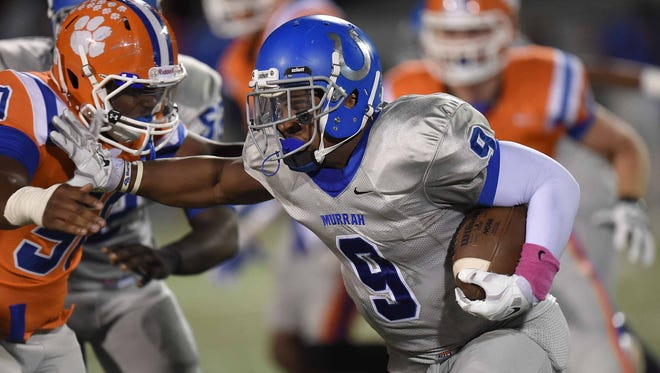 Murrah's Malik Dear uses a stiff arm against a Madison Central defender to gain extra yardage on Friday, October 3, 2014, at Madison Central.