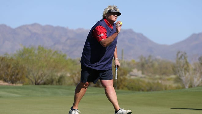 Laura Davies of England holds up the ball after a par putt on the 18th green following the third round of the JTBC LPGA Founders Cup at Wildfire Golf Club on March 22, 2014.