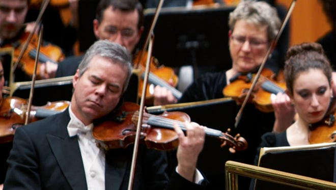 In this undated photo provided by the Milwaukee Symphony Orchestra  concertmaster Frank Almond plays a 300-year-old Stradivarius violin that was on loan to him during a concert in Milwaukee. Police said Wednesday, Feb. 5, 2014, three people have been arrested in connection with the theft of the multimillion-dollar instrument.