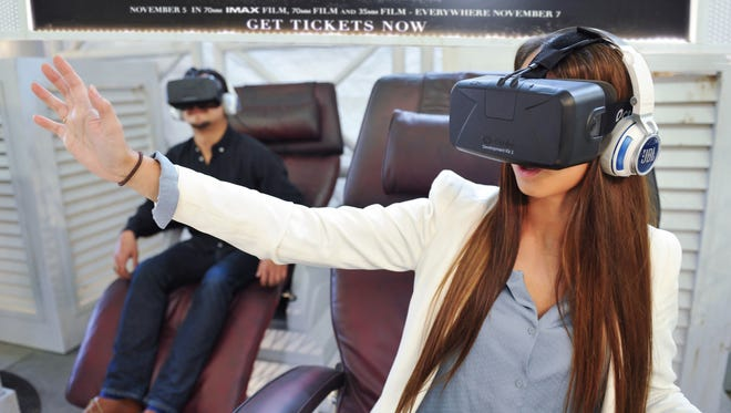 A participant in the Interstellar Oculus Rift Experience reaches for an object.