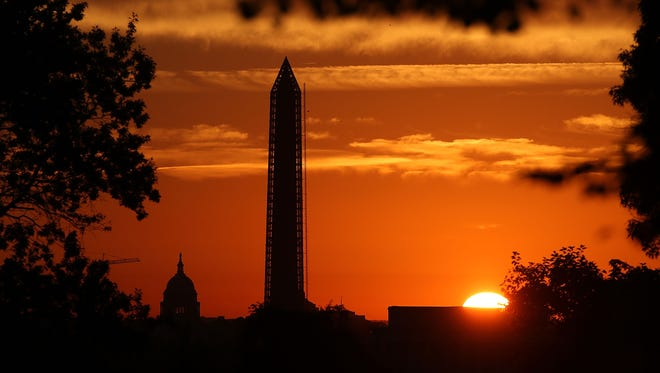 The sun begins to rise behind the U.S. Capitol and the Washington Monument on Sept. 30, 2013, in Washington, D.C.