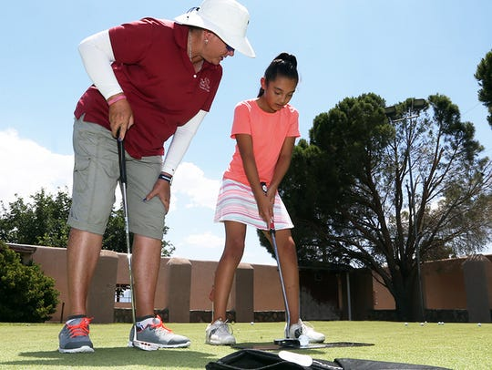 Professional golfer Kristi Albers watched the putting