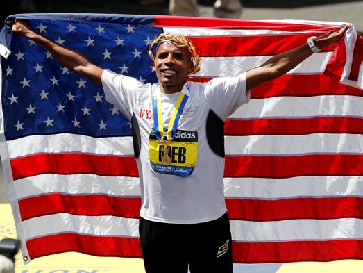 Meb Keflezighi holds up an American flag at the finish line after winning the Boston Marathon.