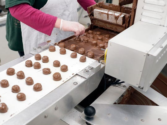 Chocolate creams on a conveyer belt are coated in milk chocolate and marked by an employee at Seroogy's Chocolates.