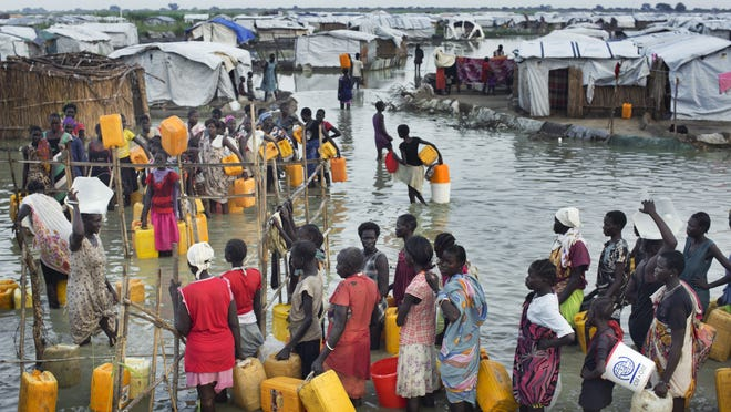 """South Sudanese women wait in knee-deep floodwaters to access fresh water from a tap at a makeshift United Nations camp for displaced people in Bentiu, South Sudan, on Monday, Sept. 22, 2014. South Sudanese at the camp are living in knee-deep, sewage-contaminated floodwater, which Doctors without Borders calls """"an affront to human dignity."""" Progress is being made in talks to curb violence that has caused ,ore than 1.3 million people to flee their homes."""