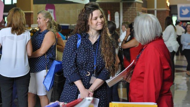 Peabody Montessori Elementary teacher Cassie Doucet talks curriculum with a vendor Monday morning at the Rapides Parish School District's 2016 Summer Institute.