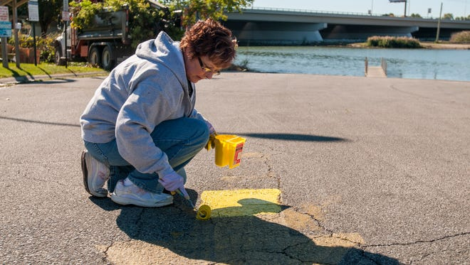 Chemical Bank employee Janet Brown paints an arrow on the cement Monday, Oct. 10, at the Riverside Boat Launch in Port Huron.