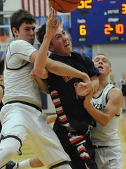 Harrison senior Eliot Champion gets hammered under the basket as the Raiders traveled to Tri-West Wednesday night.