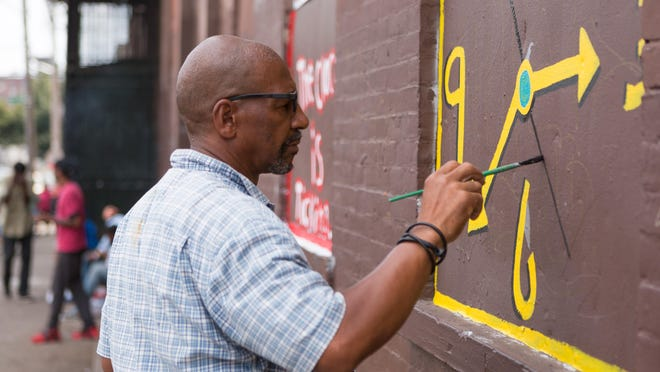 Tyree Guyton works to cover a four-story brick warehouse in Philadelphia with his trademark clock paintings.