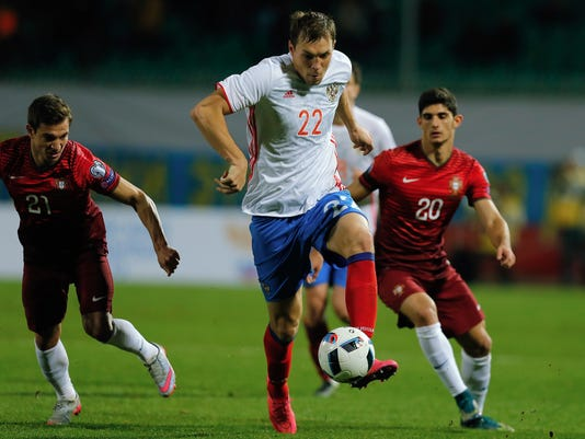 FILE - In this Saturday, Nov. 14, 2015 file photo, Russia's Artyom Dzyuba, front, fights for the ball with Portugal's Gonsalo Guedes, right, and Cedric Soares during an international friendly soccer match between Russia and Portugal in Krasnodar, Russia. Russia has suffered another blow ahead of the Confederations Cup as forward Dzyuba withdrew citing fitness concerns. (AP Photo/Alexandr Mysyakin, FIle)