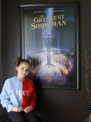 "Austyn Johnson poses in front of a poster for ""The"