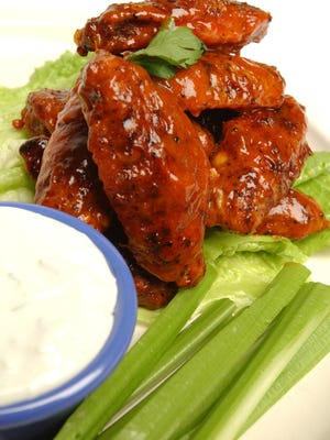 Buffalo wings served with ranch dressing for dipping and celery sticks.