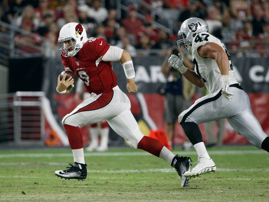 Arizona Cardinals quarterback Matt Barkley, left, scrambles