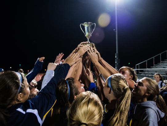 Elco hoists the Blue-Gray Cup after beating Cedar Crest