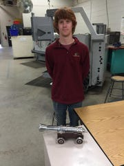 Austin Rhodes stands near his model cannon he made