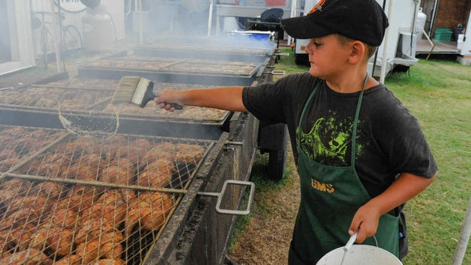Jeremiah Schrock, 8, of Greenwood, spreads sauce for the chicken being cooked at the Greenwood Mennonite School's food booth at the Delaware State Fair in Harrington.
