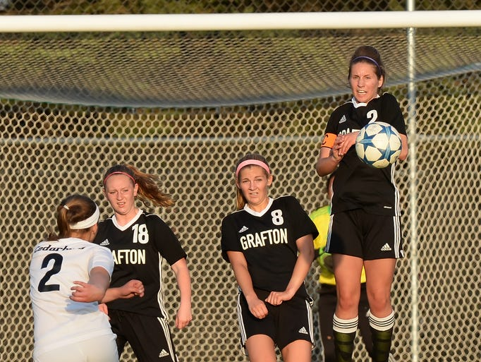 Grafton's Madelyn Depke (right) jumps up to block a