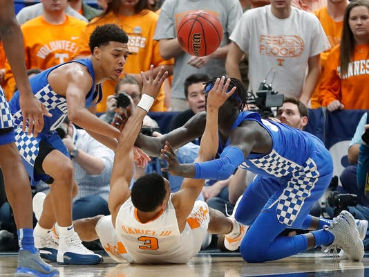 Tennessee guard James Daniel III, center, passes the ball away from Kentucky's Quade Green, left, and Wenyen Gabriel, right, during the second half of an NCAA college basketball championship game at the Southeastern Conference tournament Sunday, March 11, 2018, in St. Louis. (AP Photo/Jeff Roberson)