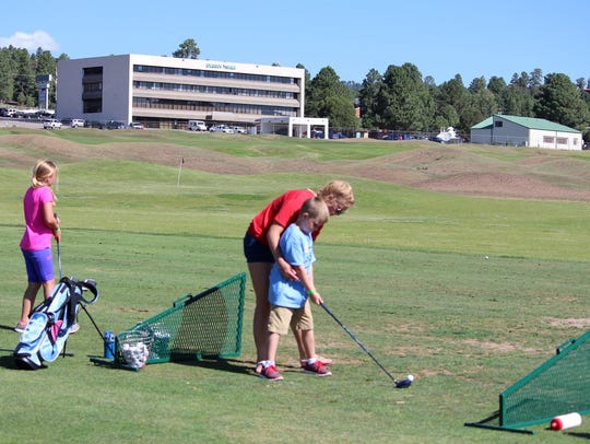 A young golfer received some help on his swing during
