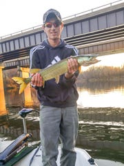 Alex Beebe holds up a muskie he caught and released