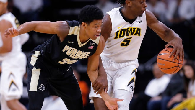 Purdue guard Nojel Eastern, left, tries to steal the ball from Iowa forward Tyler Cook (5) during the second half of an NCAA college basketball game, Saturday, Jan. 20, 2018, in Iowa City, Iowa. Purdue won 87-64. (AP Photo/Charlie Neibergall)