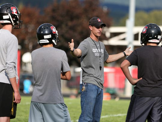 Head coach Dustin McGee, center, works with players