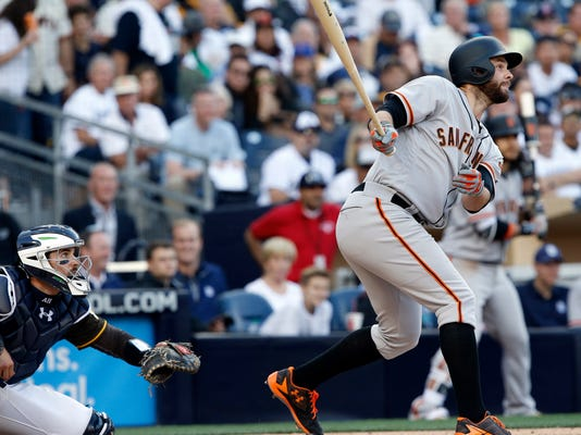 San Francisco Giants' Brandon Belt watches his grand slam in front of San Diego Padres catcher Austin Hedges during the fifth inning of a baseball game in San Diego, Friday, April 7, 2017. (AP Photo/Alex Gallardo)