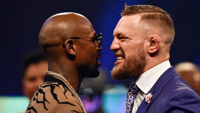 Floyd Mayweather, left, and Conor McGregor, right, face off during their world tour press conference to promote their Aug. 26 fight.