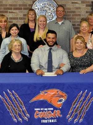 Ed Merhi is pictured with several family members as he signs his letter of intent to play college football for Concordia University.