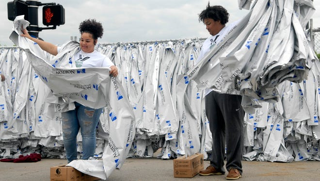 Volunteers from Waggener High School, Lexy Marshall, 16, left, and Ivan Hill, 18,  prepare blankets for the runners before the start of the Kentucky Derby Festival Marathon and miniMarathon downtown Saturday April 30, 2016.