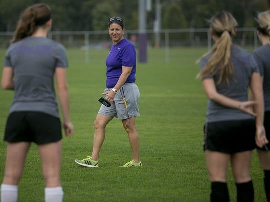 University of Wisconsin-Stevens Point women's soccer coach Dawn Crow, center, who was part of four NCAA Division I national championships at North Carolina, speaks to her players before a recent practice at the Point Soccer Bowl. The first-year coach is intent on returning the Pointers to prominence.