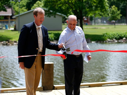 City manager Joe Moore and Mercury Marine president John Pfeifer cut a ribbon symbolizing the opening of a new dock on Oven Island in Lakeside Park. The dock, mostly funded by Mercury Marine, will be the new weigh-in location for the Walleye Weekend fishing competition this month.