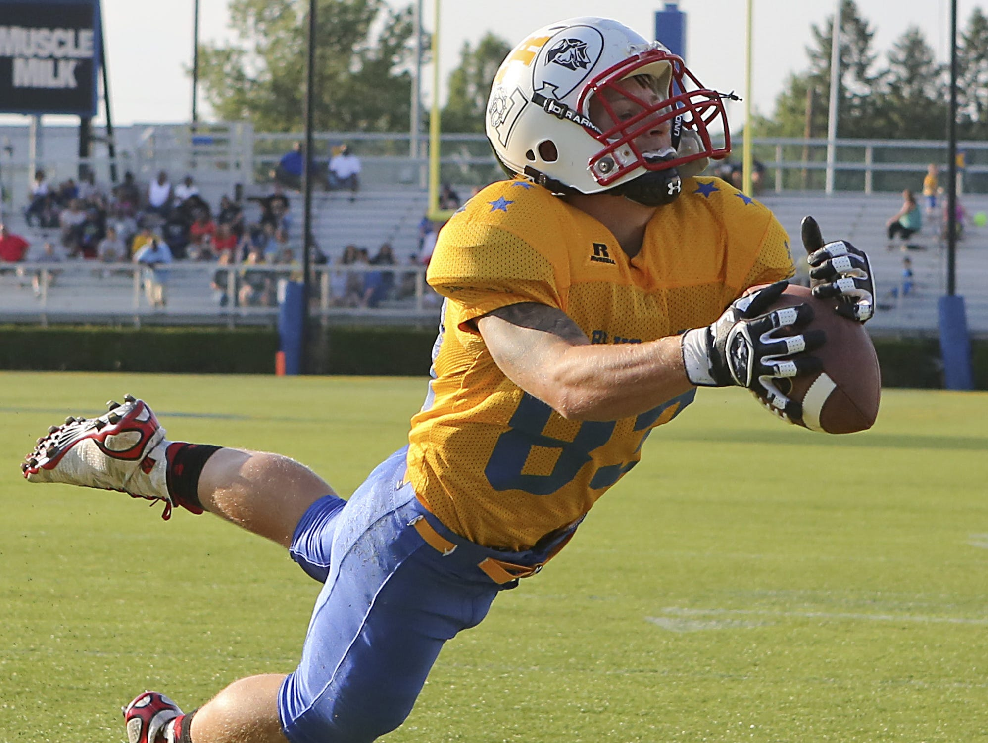 Smyrna's Brandon Bishop of Gold sprawls for a 15-yard touchdown reception from Dover's Triston Harris in the first half of the DFRC Blue Gold All-Star game at Delaware Stadium Saturday.