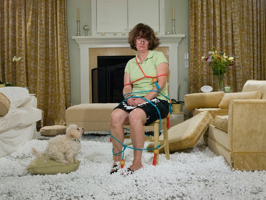 Woman tied to chair in mess of packing peanuts with dog watching in living room