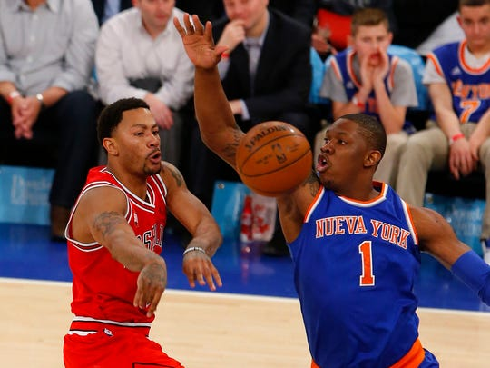 Mar 24, 2016; New York, NY, USA; Chicago Bulls guard Derrick Rose (1) passes the ball past New York Knicks center Kevin Seraphin (1) during second half at Madison Square Garden. The Knicks won 106-94.