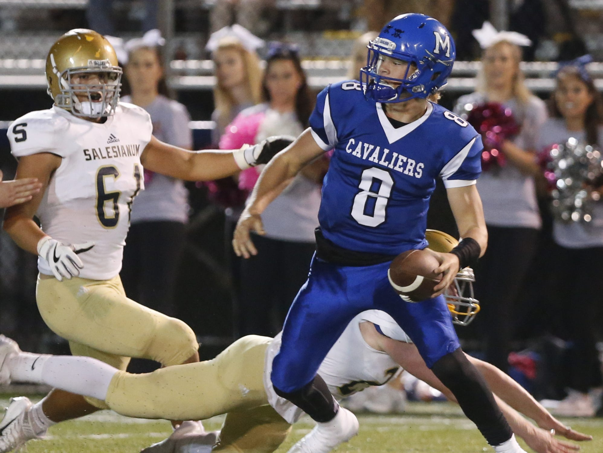 Middletown quarterback Drew Fry avoids Salesianum's Casey Spink (61) and Garrett Million before turning upfield for a 12-yard scramble and score in the first quarter at Cavalier Stadium Friday.