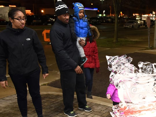 Mardita, Millan, D.J., 2, and Courtney Embry take in one of the ice sculptures at Thursday's Olde-Fashioned holidays event.