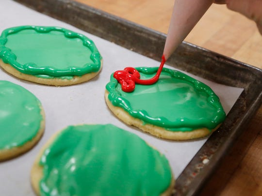 "Mary Freitag decorates wreath Christmas cookies Thursday, December 14, 2017, at O'Rears Pastry Shop, 321 N. Ninth Street in Lafayette. Freitag said 25 different varieties of Christmas cookies are baked at O'Rears for the holidays. ""It's my favorite time of year,"" she said."