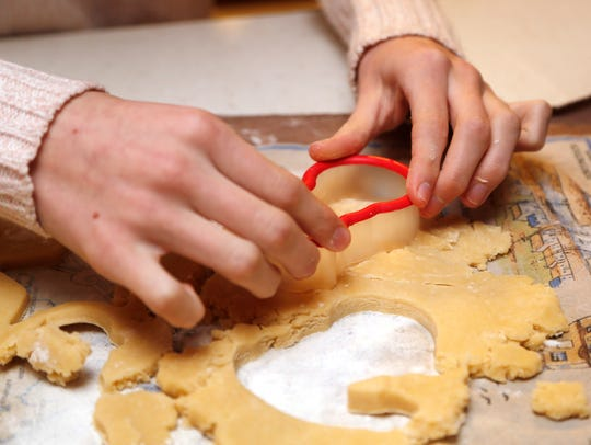Annabel Prokopy, 13, uses a cookie cutter to make Christmas