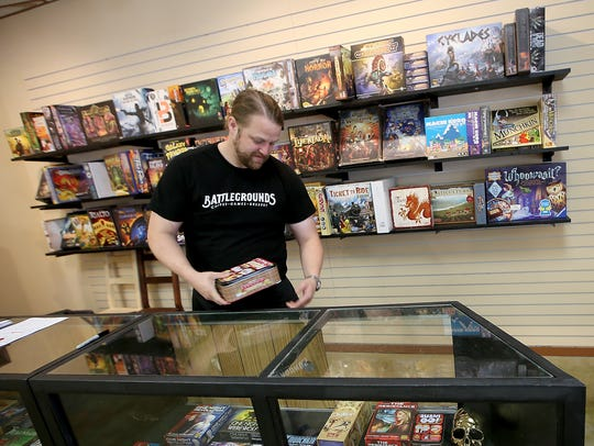 Joshua Albin removes the game Sushi Go Party from the game counter at Battlegrounds Cafe in downtown Poulsbo.
