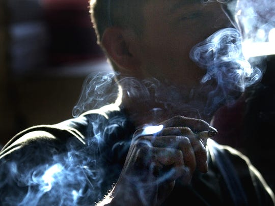 A smoker exhales smoke from his cigarette.