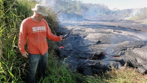 In this photo provided by the U.S. Geological Survey, a geologist marks the coordinates of the Kilauea lava flow front with a GPS unit. A 13-mile finger of lava from Kilauea Volcano has started to again move quickly, and could hit a secondary road sometime Friday. Officials on Hawaii's Big Island won't start evacuating people until the lava flow is within three to five days of affecting Pahoa residents.