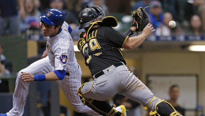 The Brewers' Christian Yelich avoids the tag of Pirates catcher Francisco Cervelli to score during the sixth inning Friday night at Miller Park.