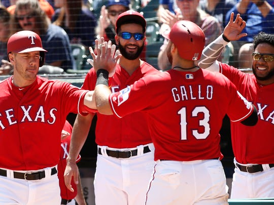 Texas Rangers' Joey Gallo (13) is congratulated by Patrick Wisdom, left, Nomar Mazara and Elvis Andrus, right, after he scored on a sacrifice fly by Hunter Pence against the Houston Astros during the first inning of a baseball game Sunday, April 21, 2019, in Arlington, Texas. (AP Photo/Mike Stone) ORG XMIT: ARL109