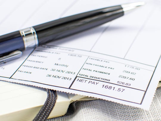 Wage slip on pad with black pen