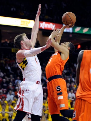 Syracuse guard Tyler Ennis, right, shoots as Maryland forward Evan Smotrycz, left, defends during the first half of an NCAA college basketball game.