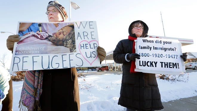 Jane Gaffney and Claire Ditter of Fond du Lac protest with about 50 other people angry with President Donald Trump's executive order on the corner of Main and Johnson Streets in the city of Fond du Lac Wednesday evening.